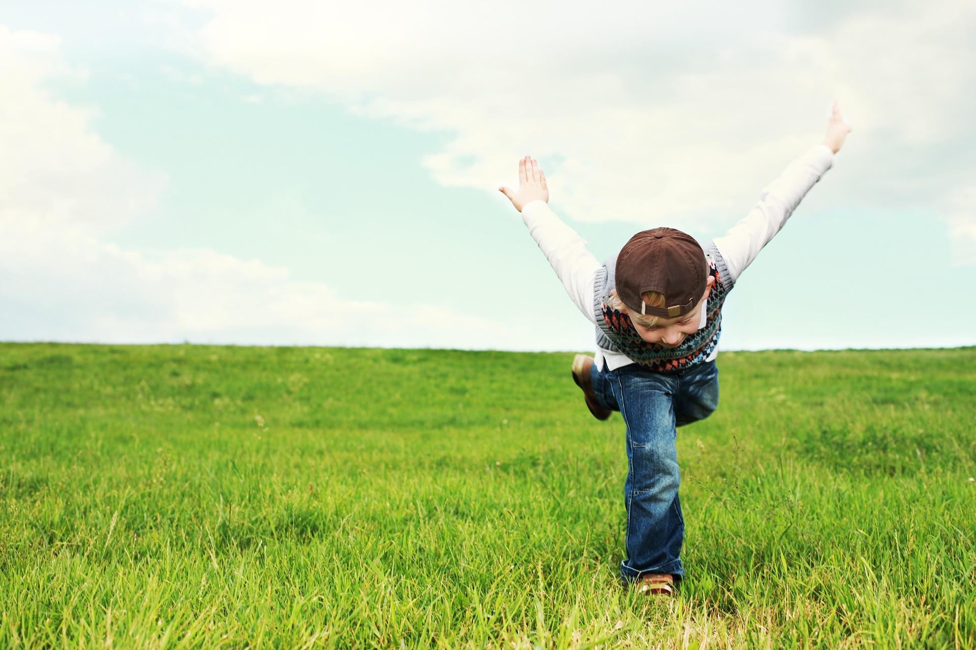 Krepko zdravje prinaša številne prednosti - tudi lahkotnost bivanja kot simbolizira mladi fant na sliki sredi travnika